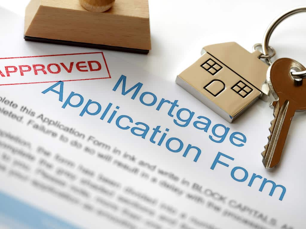 approved mortgage application form with house keys sitting on top