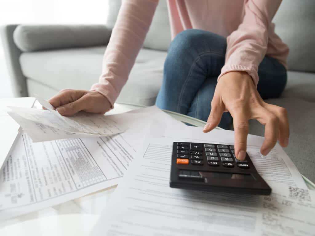 documents strewn across a coffee table as a woman calculates bills