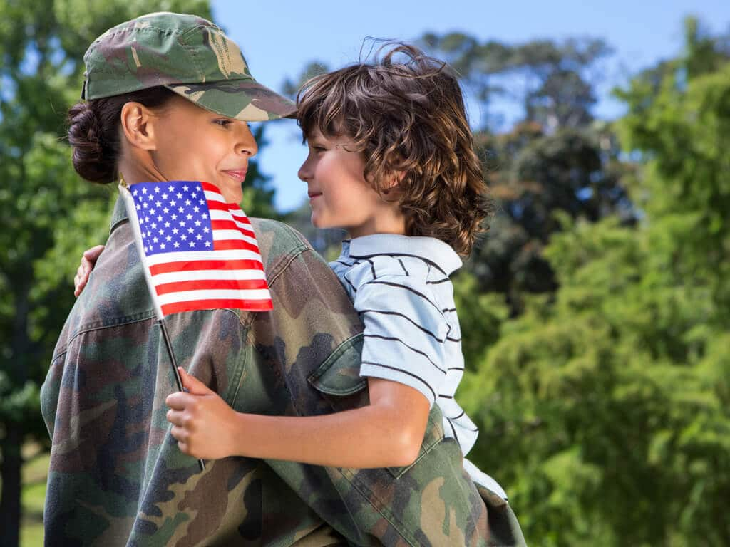 female military service member holding young boy waving american flag