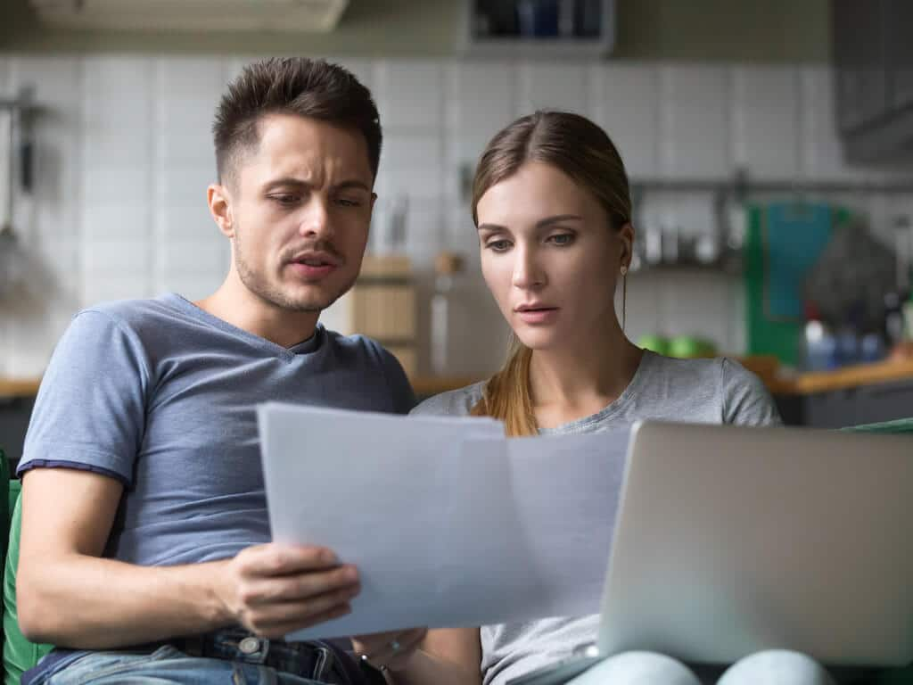 distressed couple looking over bank statements