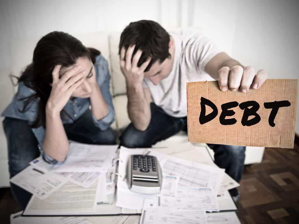 distressed man and woman reviewing bills and holding debt sign