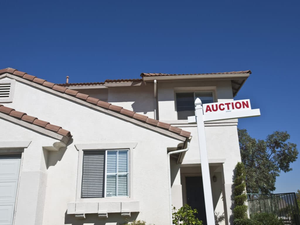 house with an auction sign in the front yard