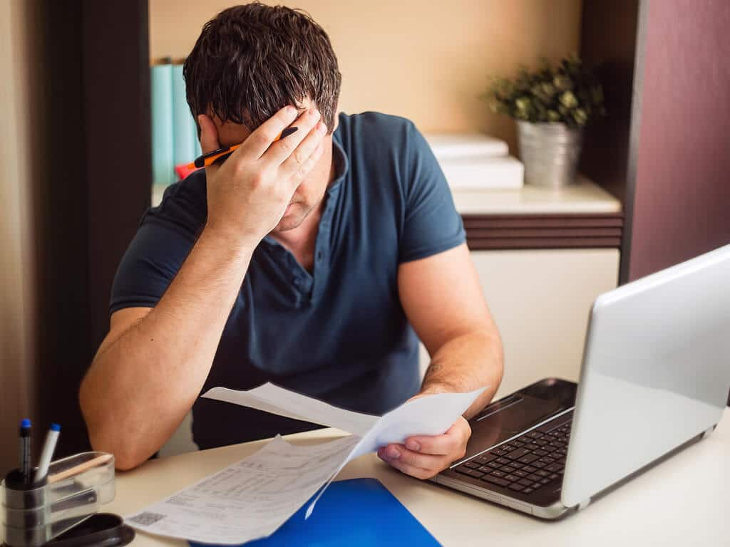 upset man reading legal documents in front of a laptop