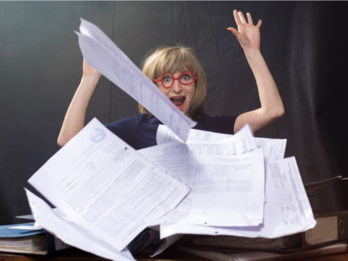 woman throwing hands up from paperwork