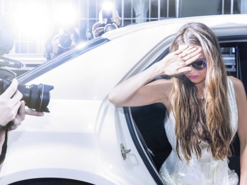 celebrity covering face and being photographed getting out of a car