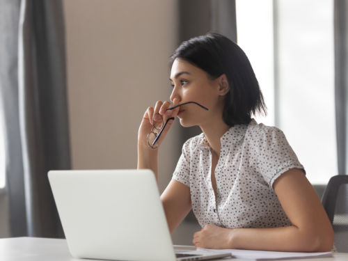 woman holding glasses up to mouth and thinking in front of laptop