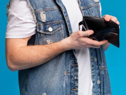 man in jean jacket holding empty wallet