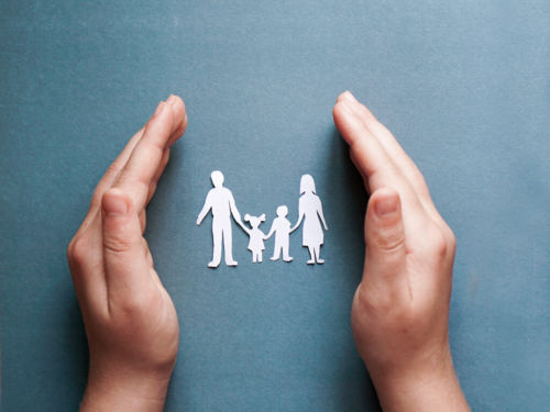 paper cutout of a family in between hands on a blue background