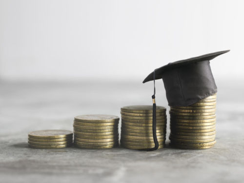 stack of gold coins topped with a mini graduation cap