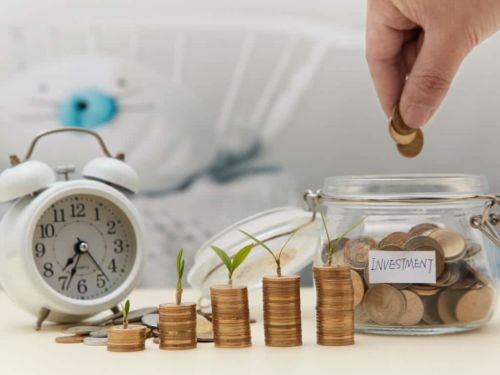 pennies in a jar labeled investment next to an alarm clock