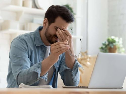 upset man pinching his nose and holding his glasses by his laptop