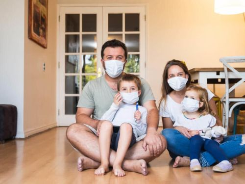 family sitting together while wearing masks