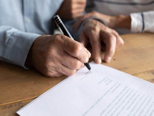 elderly man signing legal documents