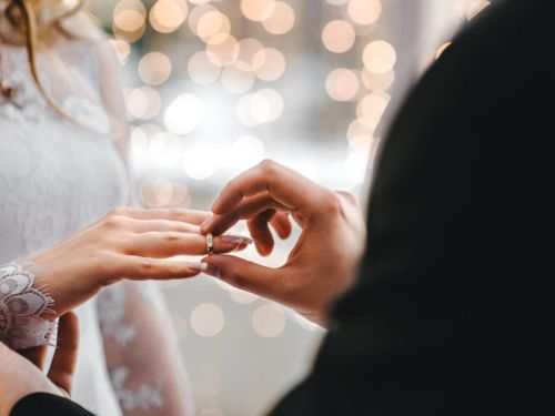 wedding ring being placed on the brides finger during wedding