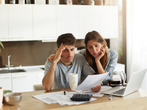 worried couple looking at bill