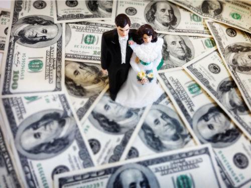 wedding figurines on top of 100 dollar bills
