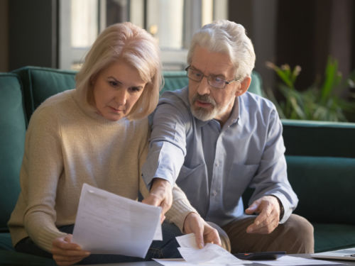 elderly couple looking at document